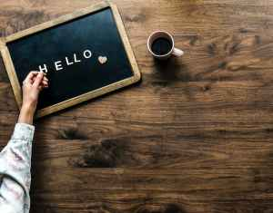 person s hand on black board with hello text beside brown mug