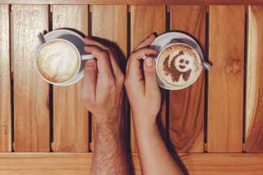 person holding cup of coffees on table